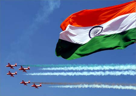 The Surya-Kiran aerobatic team of the Indian Air Force flies past the Indian flag.