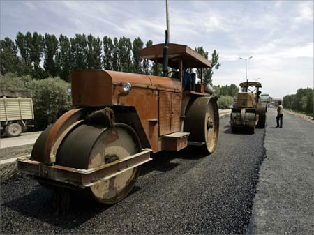 Workers use road rollers during the rebuilding process of a road.