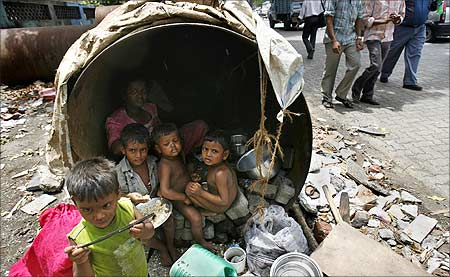 Children eat in their his make-shift home in an unused waterpipe in Mumbai.