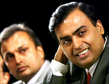Mukesh Ambani (R) and Anil Ambani listen to a shareholder speak during the company's Annual General Meeting (AGM) in Bombay June 24, 2004.