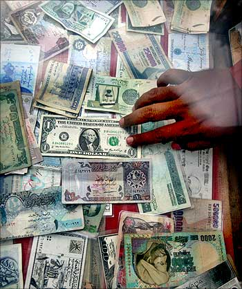 A currency dealer displays various currencies at his roadside money changer stall.