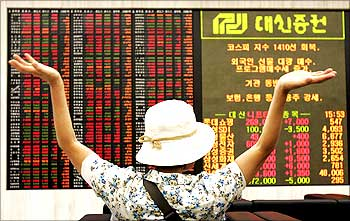 An investor stretches herself as she looks at stock price index in Seoul.