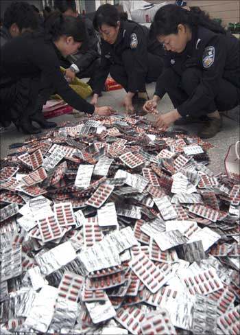 Policemen check confiscated fake drugs in Xuchang in China.