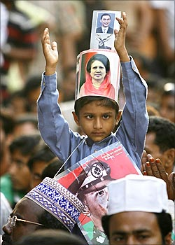 A boy with a picture of Begum Khaleda Zia around his head claps.