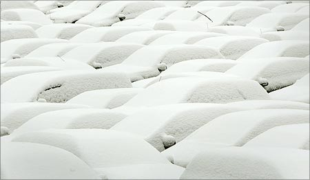Snow covered cars are parked at a car park.