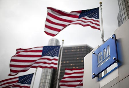 Flags wave behind a General Motors Corp sign in downtown in Detroit.