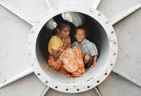 A homeless woman and her son take shelter inside a pipe in Kolkata.