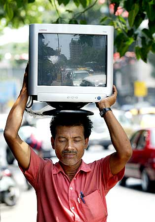 A worker carries a new computer terminal to an office.
