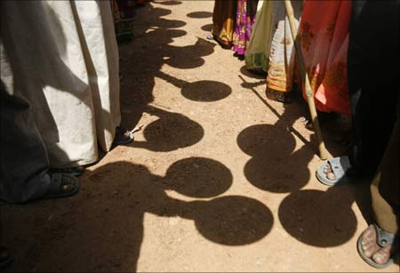 Villagers hold empty plates as they stand in front of the office of a block development officer in Galsi village near Kolkata.