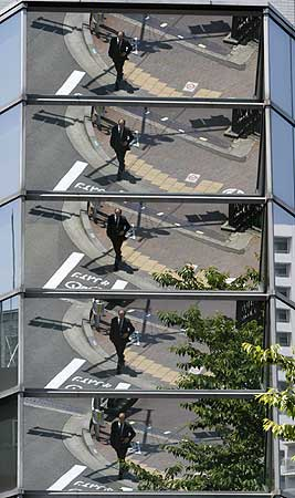 A businessman is reflected on an office building in Tokyo.