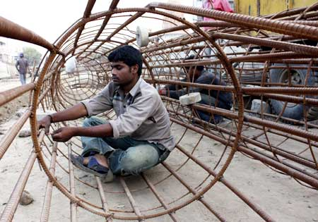 Labourers work at a commercial construction site in Ahmedabad.
