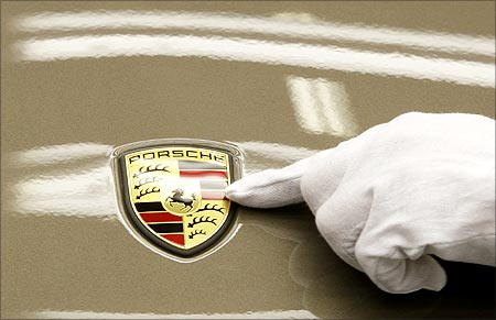 A worker inspects the logo on a car.