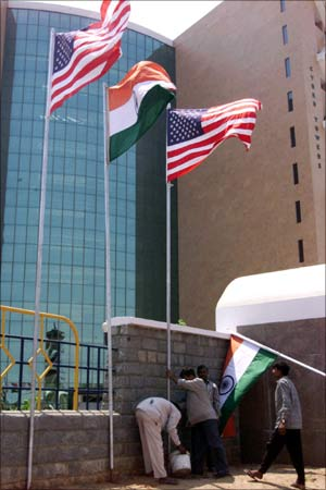 Workers at 'High Tech City', a building where software companies are situated put up Indian and American flags in Hyderabad.