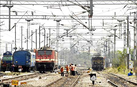 Railway employees work on a railway track in Hyderabad