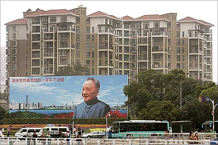 Apartments are seen behind a billboard of late Deng Xiaoping in Shenzhen.