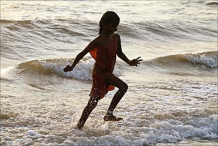 A tourist runs on a beach in the town of Velankanni near Chennai.