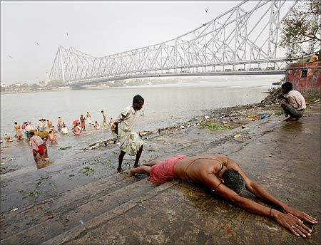 A Hindu devotee prays on the bank of the Ganges river against the backdrop of Howrah Bridge.