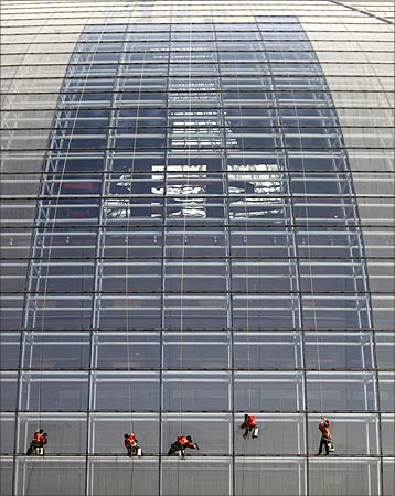 Workers clean the exterior of the National Grand Theatre, nicknamed the 'egg', in Beijing.