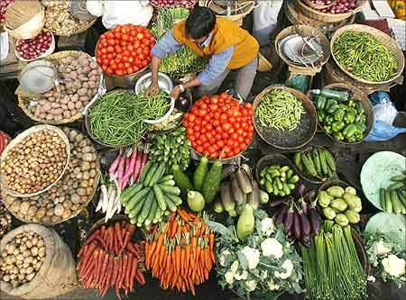A vendor arranges vegetables at a market in Siliguri, West Bengal
