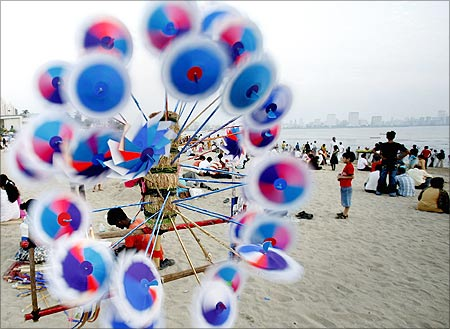 A vendor sells paper windmills at a beach in Mumbai.