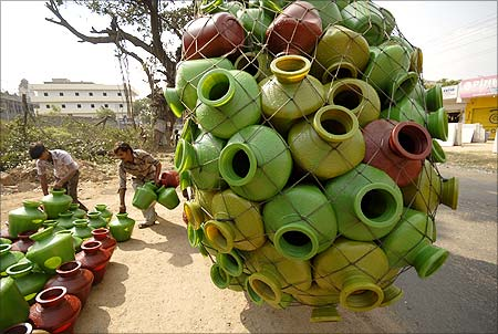 Roadside vendors unload plastic pitchers for sale from a vehicle on the outskirts of Hyderabad.