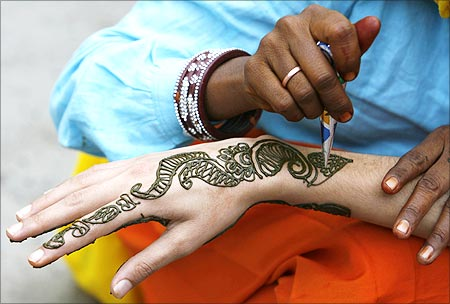 A vendor applies henna designs on the hand of a Kashmiri girl in Srinagar.