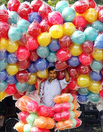 A street vendor walks with plastic balls at a fair ground in New Delhi.