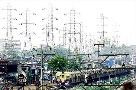 A suburban passenger train goes past a network of high voltage electric transmission towers in Mumbai.