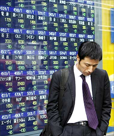 A man walks past a stock index board outside a brokerage in Tokyo.