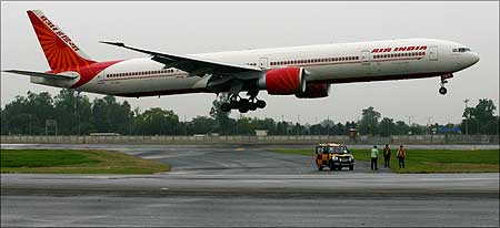 Members of the ground staff watch the inaugural flight of an Air India Boeing 777.