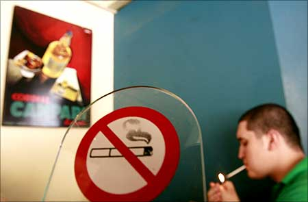 A man lights a cigarette in front of a smoking ban sign in a cafe in Chalandri suburb, north of Athens.