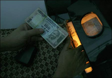 A man uses an electronic machine to check an Indian currency note at a money exchange shop in Siliguri.