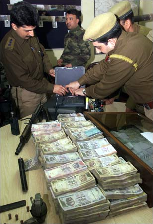 Indian police officers examine seized currency notes in Srinagar.