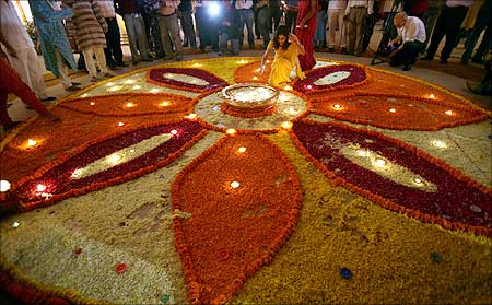 A woman lights up lamps in a flower decoration during Diwali mahurat special trading at the Bombay Stock Exchange (BSE).