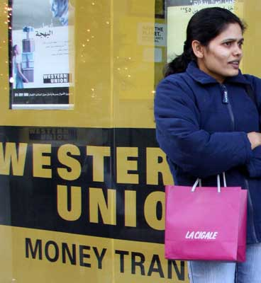 A foreign worker stands in front of Western Union, a money transfer agency in Dora, east of Beirut.