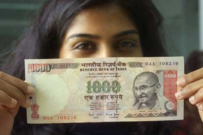 A woman displays a Rs 1,000 note.