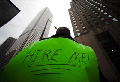 A jobseeker, with a sign strapped to his back, tries to attract the attention of potential employers as he hands out resumes.