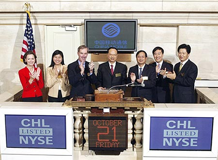 China Mobile chairman and CEO Wang Jianzhou (centre) rings the opening bell at the New York Stock Exchange