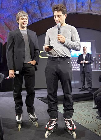 Larry Page (L) and Sergey Brin, founders of Google, show the new G1 phone running Google's Android software in New York
