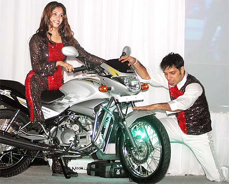 Models pose with the 125 cc 'Glamour' Hero Honda motorcycle.