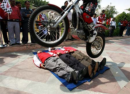 Honda's trial bike rider Motoharu Honda performs a stunt over volunteers during an event of Honda Motorcycle and Scooter India (HMSI) in New Delhi
