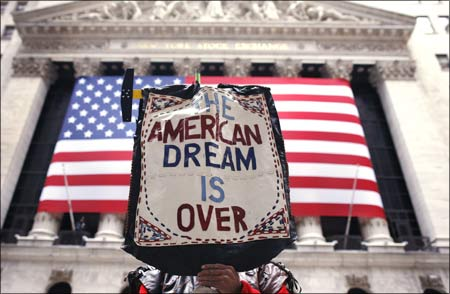 A demonstrator holds a sign reading The American dream is over during a rally outside Wall Street in New York.