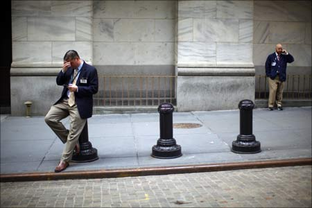 Traders stand outside the New York Stock Exchange even as the US goes through major economic turmoil.