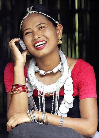 A girl from the Dhimal tribe, one of India's smallest tribal communities, talks on her mobile phone.