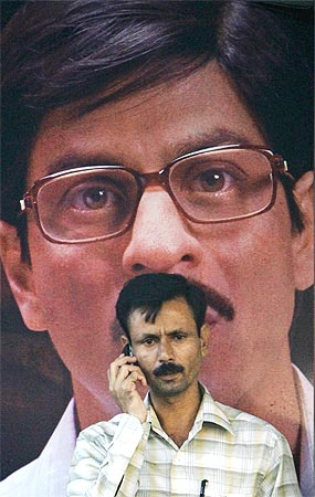 A man speaks on his mobile phone in front of a poster of Bollywood actor Shah Rukh Khan in Mumbai.