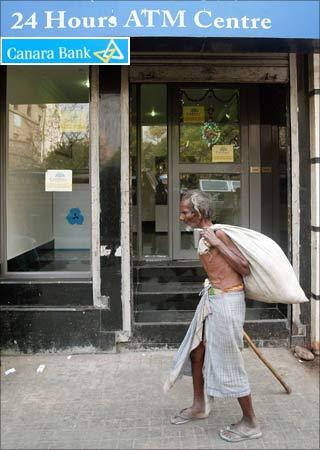A man walks past a bank's ATM kiosk in Kolkata. (Inset: Canara Bank logo).