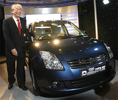 Shinzo Nakanishi, managing director of Maruti Suzuki, poses with a Maruti DZire.