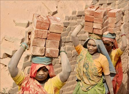 Labourers carry bricks on their heads at a brick kiln at Kodhasar village near Allahabad.