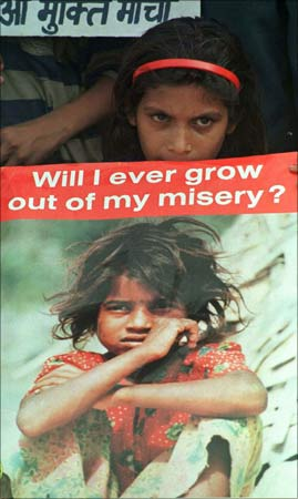 A girl child labourers holds a placard.