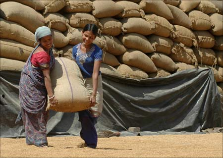 Labourers work inside a rice mill on the outskirts of Agartala.